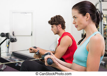 Focused brunette working out on the rowing machine