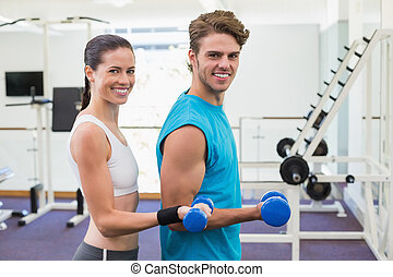 Fit couple exercising with blue dumbbells smiling at camera...