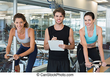 Fit women in a spin class with trainer smiling at camera at...