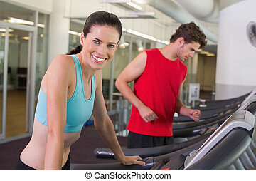 Fit happy couple running together on treadmills at the gym