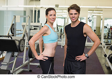 Fit man and woman smiling at camera together at the gym