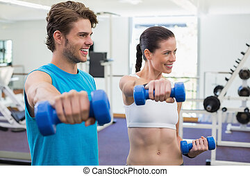 Fit couple exercising with blue dumbbells and smiling at the...