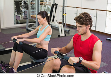 Man and woman working out on the rowing machine