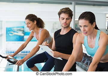 Fit women in a spin class with trainer taking notes at the...