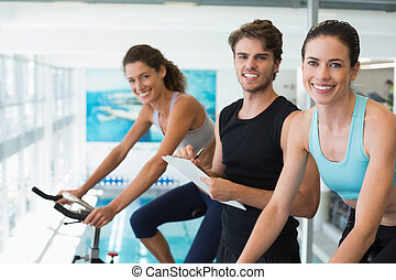 Fit women in a spin class with trainer taking notes and...