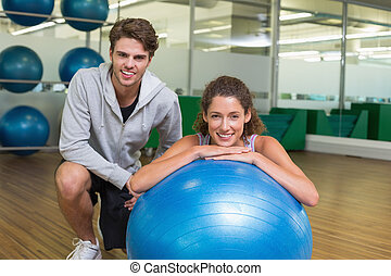 Fit woman leaning on exercise ball with trainer smiling at...