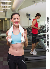 Smiling brunette with towel over shoulders at the gym