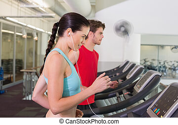 Fit couple running together on treadmills at the gym