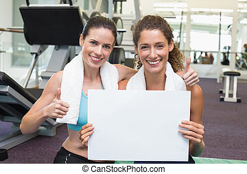 Fit friends showing white card to camera at the gym