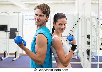 Fit couple exercising together with blue dumbbells at the...