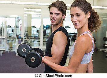 Fit couple lifting dumbbells together smiling at camera at...