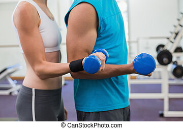 Fit couple exercising with blue dumbbells at the gym