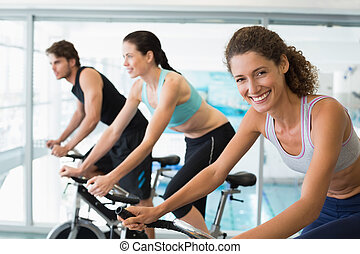 Fit people in a spin class with woman smiling at camera at...