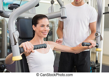 Fit brunette using weights machine for arms with trainer...