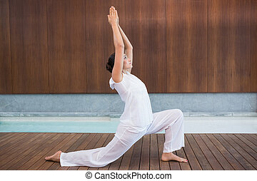 Content brunette in white doing tai chi in health spa