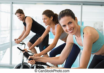 Fit people in a spin class with brunette smiling at camera...