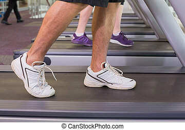 Man and woman walking on treadmills at the gym