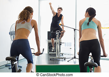Fit women doing a spin class with enthusiatic instructor at...