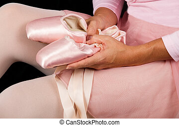 Ballerina sit down on floor  put on slippers prepare for perform