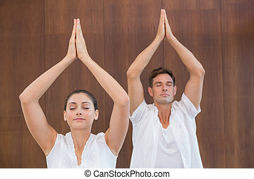 Peaceful couple in white doing yoga together with hands...