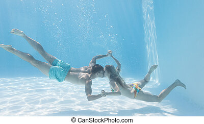 Cute couple holding hands underwater in the swimming pool on...