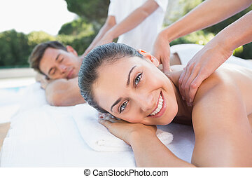 Attractive couple enjoying couples massage poolside outside...