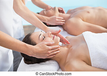 Peaceful couple enjoying couples massage poolside outside at...