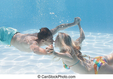 Cute couple kissing underwater in the swimming pool on their...