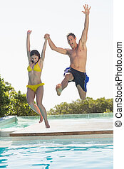 Excited couple jumping into swimming pool on holidays on a...