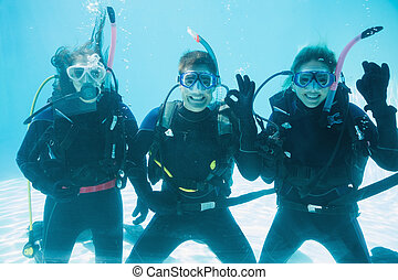 Friends on scuba training submerged in swimming pool making...