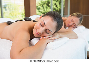 Calm friends lying on massage tables with hot stones on...