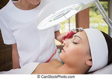 Peaceful brunette getting micro dermabrasion from beauty...