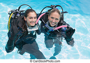 Smiling friends on scuba training in swimming pool making ok sig