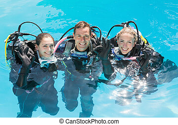Smiling friends on scuba training in swimming pool looking...