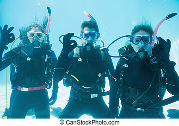 Friends on scuba training submerged in swimming pool looking...