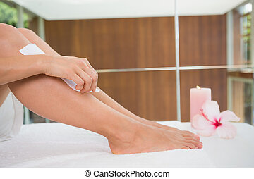 Woman waxing her legs herself in the health spa