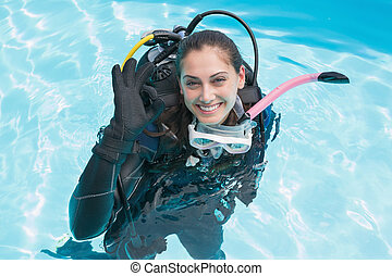 Smiling woman on scuba training in swimming pool making ok...