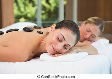 Pretty friends getting hot stone massages together in the...