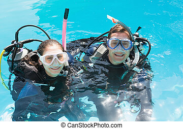 Smiling couple on scuba training in swimming pool looking at...