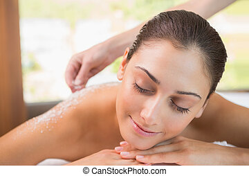 Beauty therapist pouring salt scrub on smiling womans back...