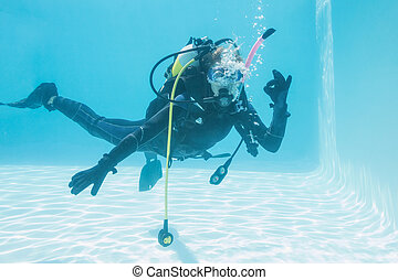 Woman on scuba training submerged in swimming pool making ok...