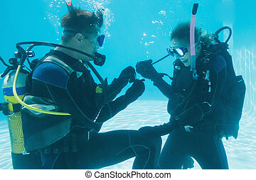 Man proposing marriage to his shocked girlfriend underwater...