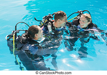 Smiling friends on scuba training in swimming pool on a...