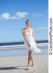 Blonde in white dress walking on the beach smiling at camera...