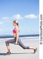 Fit woman working out with dumbbells on the beach lunging on...