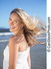 Woman in white dress smiling at camera on the beach on a...