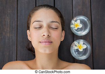 Peaceful brunette lying with eyes closed