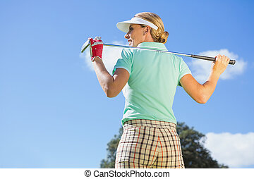 Female golfer standing holding her club on a sunny day at...