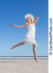 Pretty blonde in white dress leaping on the beach on a...