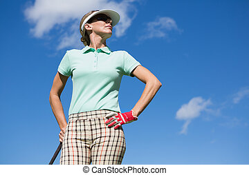 Female golfer standing with hand on hip